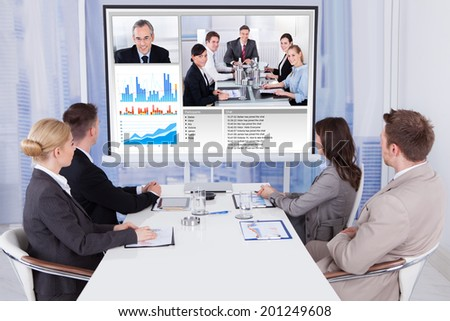 Group of business people attending video conference at table in office - stock photo