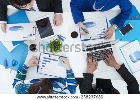 Group of business people busy discussing financial matter during meeting - stock photo