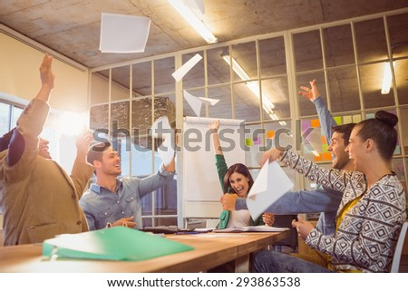 Group of business people celebrating by throwing their business papers in the air - stock photo