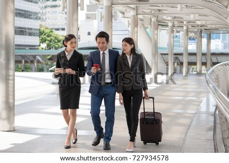 Group of business people checking flight from mobile phone during walk to check in at airport. Boss sending staff / employee to business trip conference.
