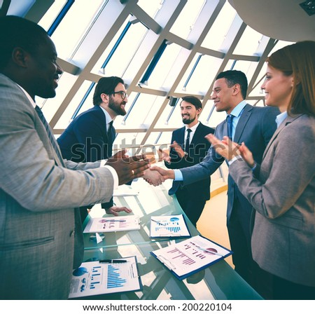 Group of business people congratulating their colleagues with promising deal - stock photo