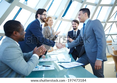 Group of business people congratulating their colleagues with striking grand deal - stock photo