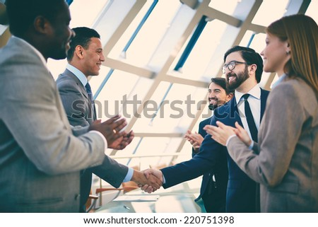 Group of business people congratulating their handshaking colleagues after signing contract - stock photo