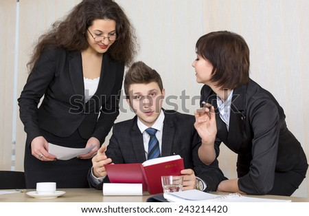Group of business people discuss working schedule Three young businesspeople, one male and two females, are having discussion with diary, charts and other office supplies - stock photo