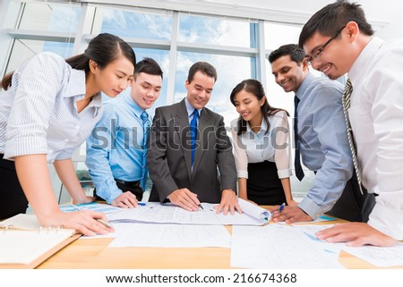 Group of business people discussing a draft of the building - stock photo