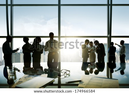 Group of business people discussing at sunrise reflected onto table with document. - stock photo