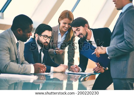 Group of business people discussing data or explaining ideas at meeting - stock photo