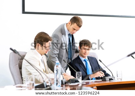 group of business people discussing documents leaning over them - stock photo