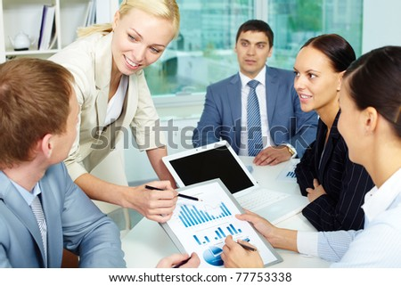 Group of business people discussing papers or sharing ideas in office
