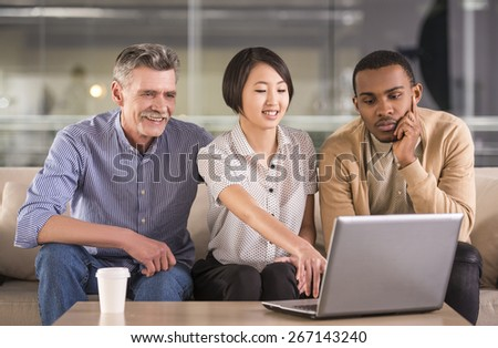 Group of business people discussing the new project on laptop at office. - stock photo