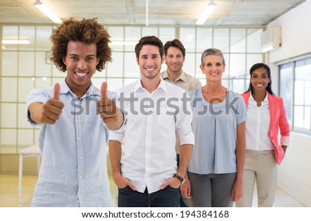 Group of business people giving thumbs up to camera in the office - stock photo