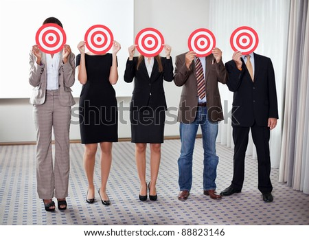 Group of business people holding a target against their faces