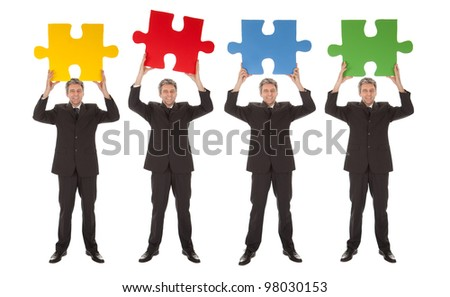 Group of business people holding jigsaw puzzle. Isolated on white