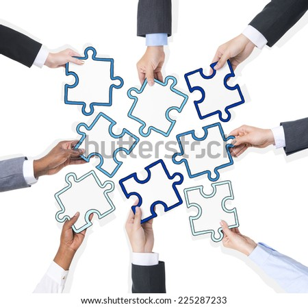 Group Of Business People Holding Pieces Of Puzzle