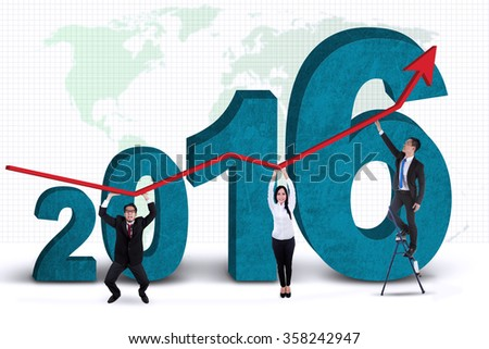 Group of business people holding upward arrow with numbers 2016 and world map background