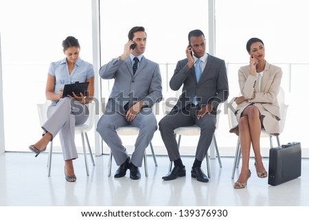 Group of business people in a waiting room using their phones and tablet - stock photo