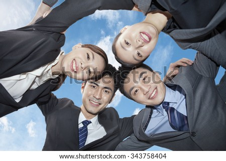 Group of business people in huddle,low angle view