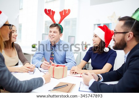 Group of business people in Santa caps and with deer horns interacting at meeting on Christmas day