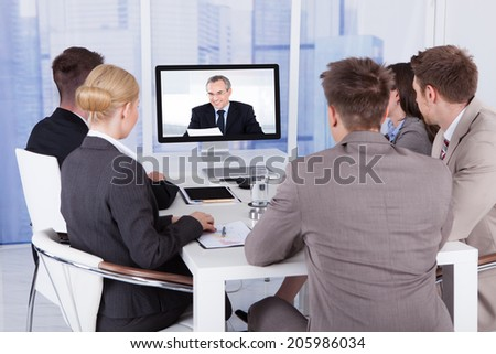Group of business people in video conference at meeting table - stock photo