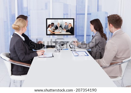 Group of business people in video conference at meeting table