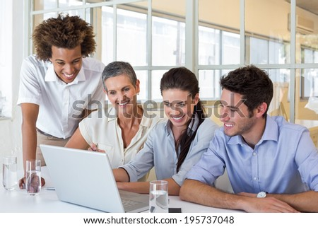 Group of business people looking at laptop in the office - stock photo