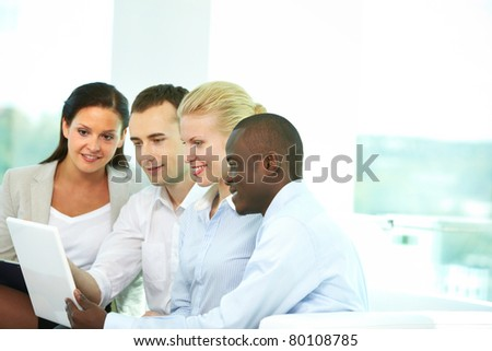 Group of business people looking at laptop screen in office - stock photo