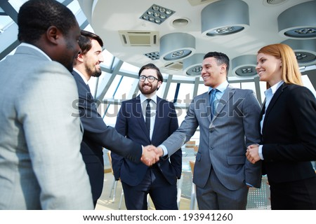 Group of business people looking at their colleagues handshaking after striking grand deal - stock photo