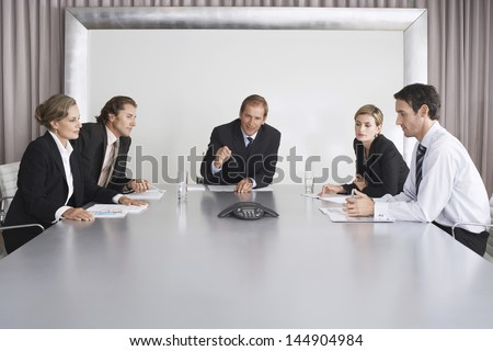 Group of business people on conference call in boardroom - stock photo