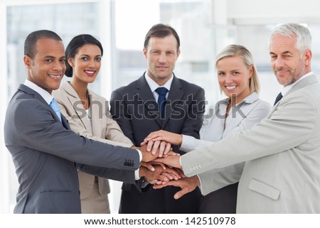 Group of business people piling up their hands together in the workplace - stock photo