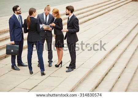 Group of business people planning work at outdoor meeting - stock photo