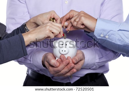 Group of business people saving money on the piggybank - stock photo