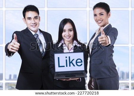 Group of business people showing like on laptop and thumbs up - stock photo