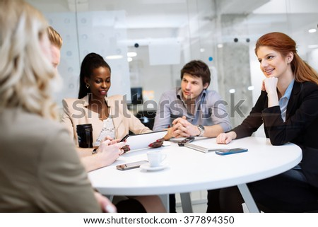 Group of business people sitting at desk and discussing new ideas