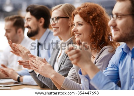 Group of business people sitting together at the table and applauding - stock photo