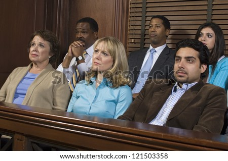 Group of business people sitting together in witness stand of court house - stock photo