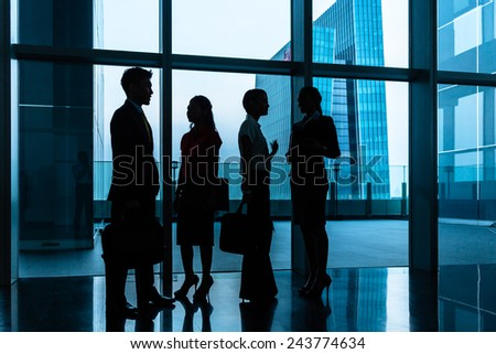 Group of business people standing in lobby or hall, a city skyline in the background, silhouette shot