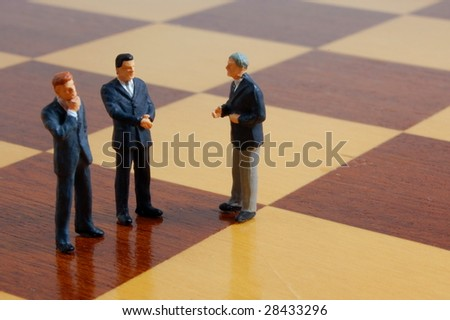 group of business people standing on a chess board