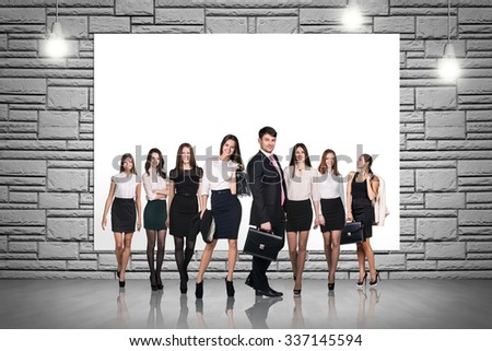 Group of business people stands on the brick wall background