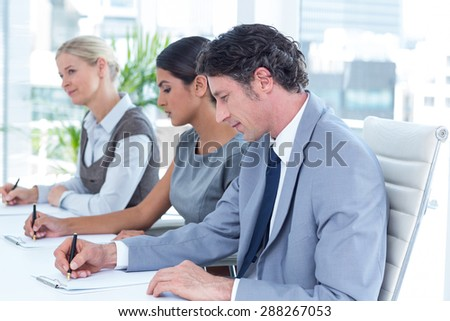 Group of business people taking notes in an office