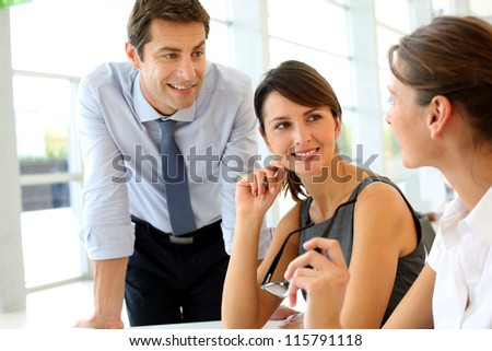 Group of business people talking around table in office - stock photo