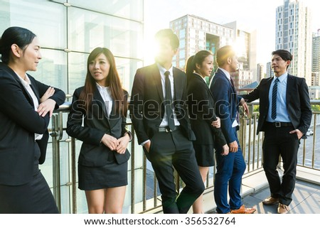 Group of business people talking outside office - stock photo