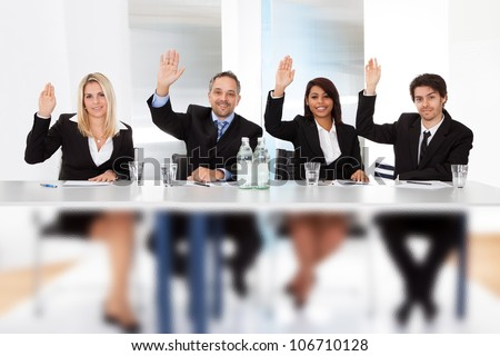 Group of business people voting at the meeting - stock photo
