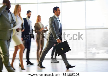 Group of business people walking in the corridor - stock photo
