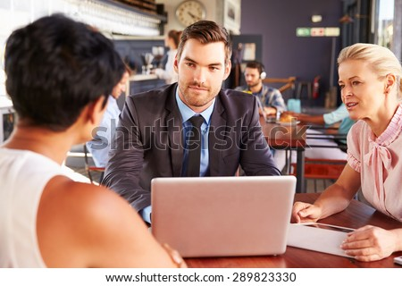 Group of business people with laptop meeting in coffee shop - stock photo