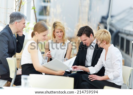 group of business people working in team outdoors in a coffee shop - stock photo