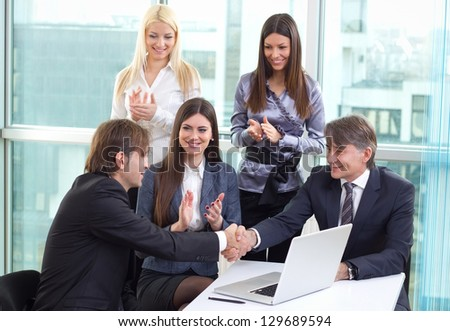 Group of business people working in the office on laptop and congratulating office co-worker on job well done - stock photo