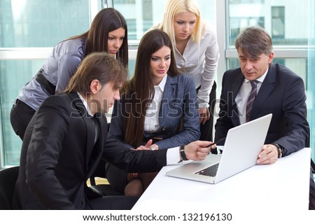 Group of business people working in the office on laptop and tablet discussing work
