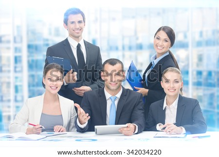 Group of business people working while sitting at the table, blue background. Concept of teamwork and cooperation - stock photo