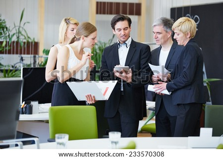 Group of business people working with tablet PC in office - stock photo