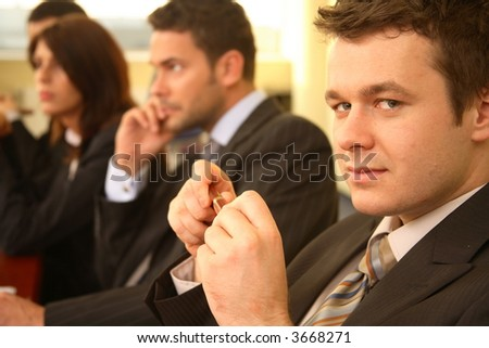Group of business persons in suits sitting at a conference table, taking part in a meeting and/or presentation - one man in focus, portrait - stock photo